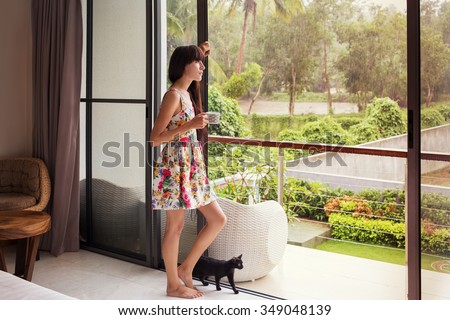 Beautiful Young Woman near big Window with black cat  holding cup and relax inside home - stock photo