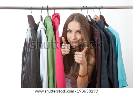 Beautiful young woman near rack with hangers - stock photo
