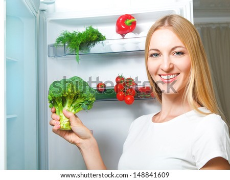 Beautiful young woman near refrigerator with broccoli