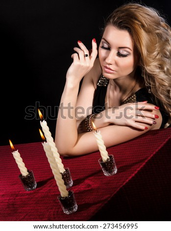 Beautiful young woman near the candles over black background - stock photo