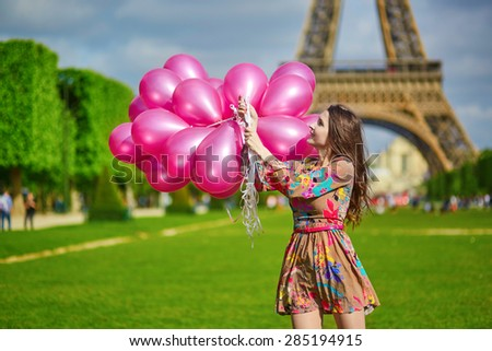 Beautiful young woman near the Eiffel tower in Paris with huge bunch of pink balloons, celebrating her birthday or other event - stock photo