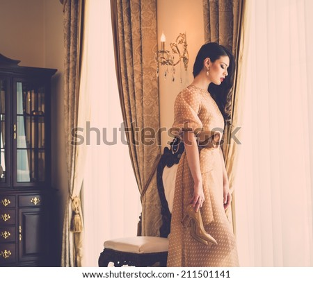 Beautiful young woman near window in luxury house interior