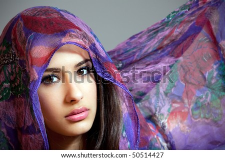 Beautiful young woman of multiple ethnicity in a glamor/fashion pose with a shawl partially covering her face on a gray background.