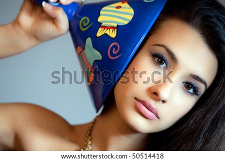 Beautiful young woman of multiple ethnicity in a glamour/fashion pose holding a large blue martini glass next to her face with a gray background.