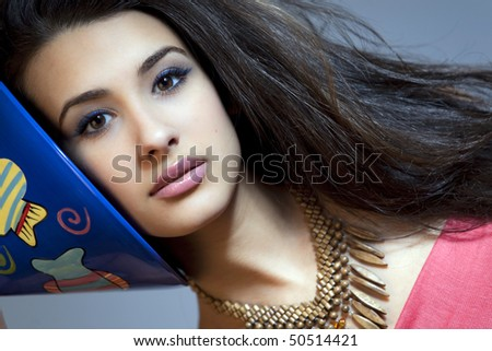 Beautiful young woman of multiple ethnicity in a glamour/fashion pose holding a large blue martini glass next to her face with a gray background. - stock photo