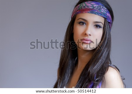 Beautiful young woman of multiple ethnicity in a glamour/fashion pose wearing a blue bandanna in a retro 1960s hippie chick pose.