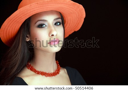 Beautiful young woman of multiple ethnicity in a glamour/fashion pose wearing a red hat with a black background.