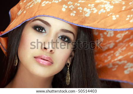 Beautiful young woman of multiple ethnicity in a glamour/fashion pose with a scarf over her head with a black background.
