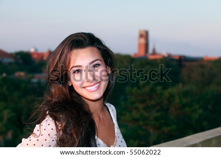 Beautiful young woman on a balcony overlooking a university campus.