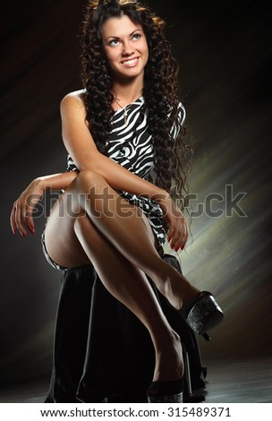 beautiful young woman on a chair. beautiful figure, long hair, bright emotions - stock photo