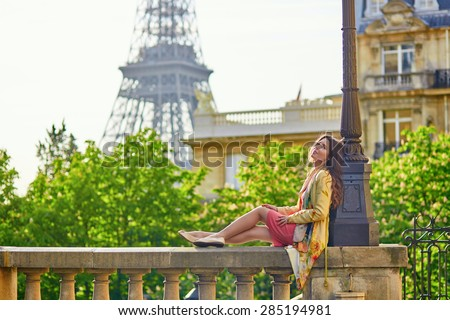 Beautiful young woman on a street near the Eiffel tower in Paris