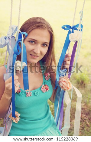 Beautiful young woman on a swing, tinted - stock photo