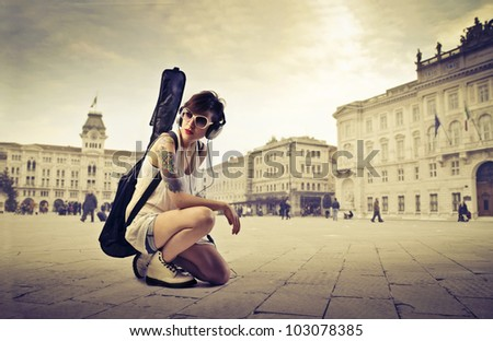 Beautiful young woman on a town square carrying a guitar case on her shoulders - stock photo