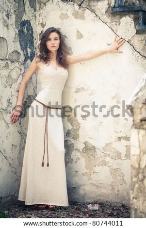 Beautiful young woman on background of old wall - stock photo