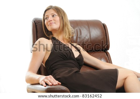 Beautiful young Woman on brown leather chair - stock photo