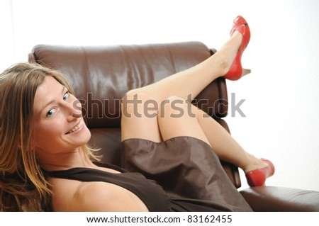 Beautiful young Woman on brown leather chair showing her long legs - stock photo