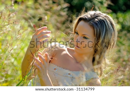 beautiful young woman on field in summer