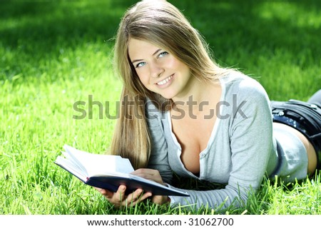 beautiful young woman on field in summer and read book