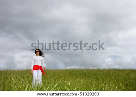 beautiful young woman on field with a red scarf - stock photo