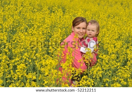 beautiful young woman on rapeseed field with baby