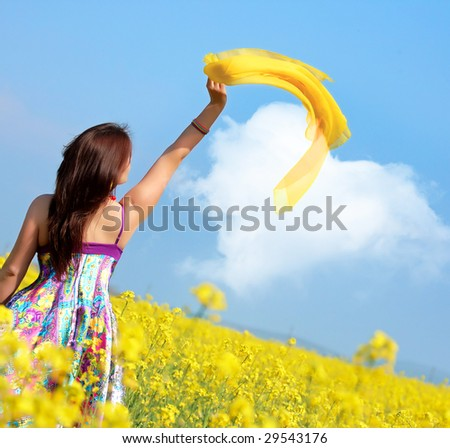beautiful young woman on rapeseed field with yellow scarf - stock photo
