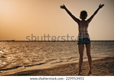 Beautiful young woman on the beach holding hands above the head. warm summer evening sunshine. arid landscape. Happy Woman in a short dress enjoys in Sea Sunset. In the background sea, vintage color - stock photo