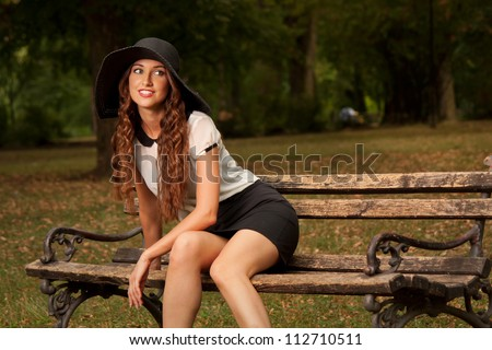 Beautiful young woman on the bench - stock photo