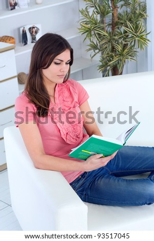 beautiful young woman on the couch with a book
