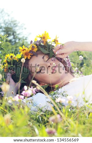 beautiful young woman on the meadow with white flowers on a warm summer day