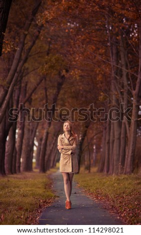 beautiful young woman on the road among the autumn trees - stock photo