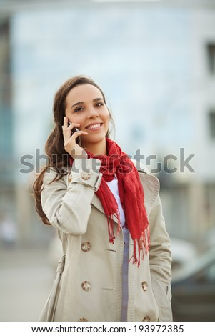 Beautiful young woman on the street on the phone - stock photo