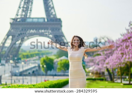 Beautiful young woman on Trocadero view point near the Eiffel tower in Paris, cheerful and happy to be there - stock photo