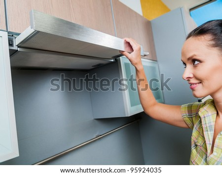 beautiful young woman open the kitchen hood at home - stock photo