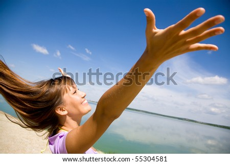 beautiful young woman opened her hands with delight at the blue sky - stock photo