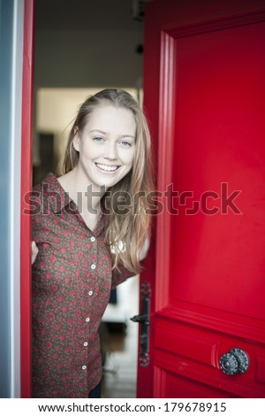 beautiful young woman opening a red door to welcome someone - stock photo