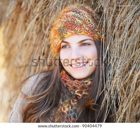 Beautiful young woman outdoor in autumn leaning against a hay stack. - stock photo