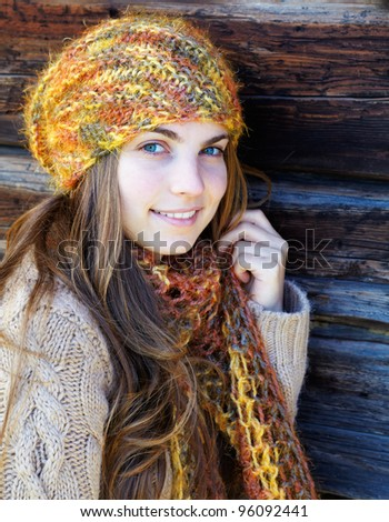 Beautiful young woman outdoor sitting at the shade, looking at camera and smiling, in autumn. - stock photo