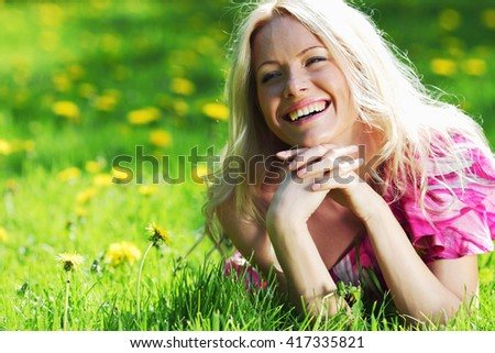 Beautiful young woman outdoors lying on green grass - stock photo
