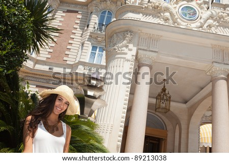 Beautiful young woman outside a classic hotel in the French Riviera. - stock photo