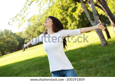 Beautiful young woman outstretching arms and smiling, shallow depth of field - stock photo