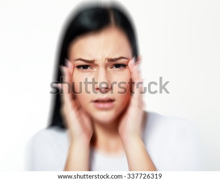 beautiful young woman over white with blurred vision and trouble focusing, trying to get focus on eyes with hands - stock photo