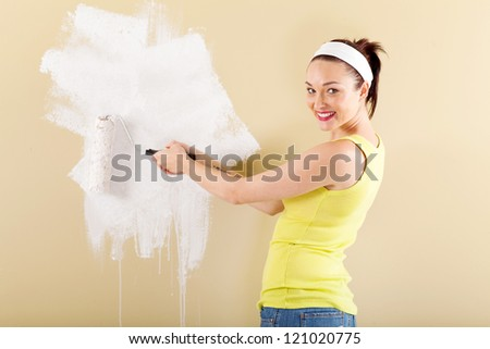 beautiful young woman painting new home with roller - stock photo