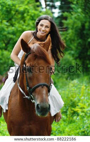 beautiful young woman park riding horse - stock photo