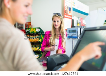 Beautiful young woman paying for her groceries at the counter of a grocery store/supermarket (color toned image) - stock photo