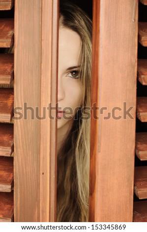 Beautiful young woman peeking - stock photo