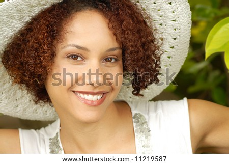 Beautiful young woman peeking from a tree in a garden - stock photo
