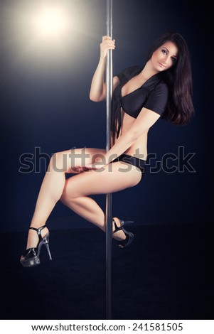 beautiful young woman performing on pole - stock photo