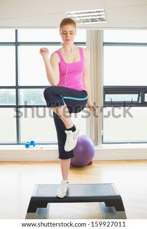 Beautiful young woman performing step aerobics exercise in a gym