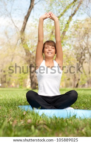 beautiful young woman performs a sport exercises in the park