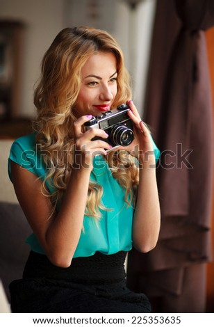Beautiful young woman photographer taking pictures with retro film camera, indoors - stock photo